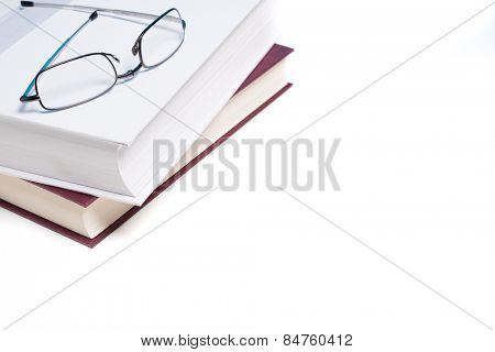 Stack of books and a pair of reading glasses on white background