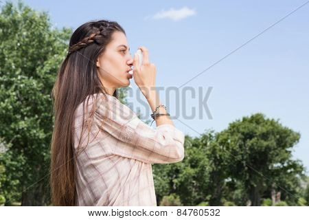 Pretty brunette using her inhaler on a sunny day
