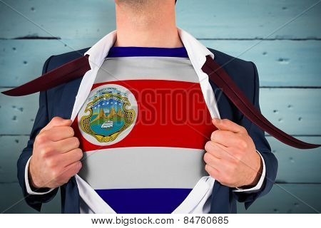 Businessman opening shirt to reveal costa rica flag against painted blue wooden planks