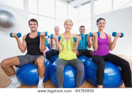 Portrait of happy people sitting on balls and lifting weights in fitness club