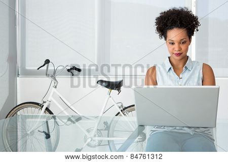 Portrait of beautiful young casual woman using laptop in office