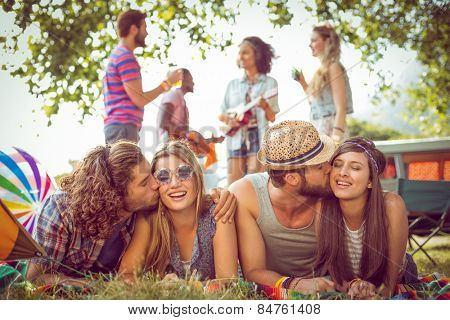 Happy hipster couples on campsite at a music festival