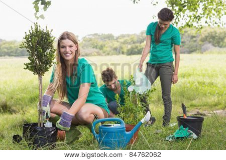 Happy friends gardening for the community on a sunny day