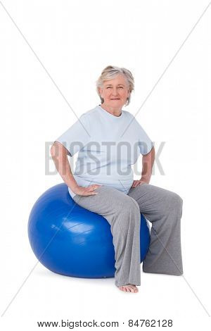 Senior woman sitting on exercise ball on white background