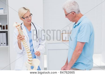 Female orthopedic doctor explaining anatomical spine to senior man in clinic