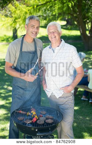 Happy man doing barbecue with his father on a sunny day