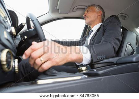 Handsome businessman in the drivers seat in his car
