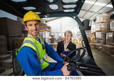 Warehouse worker and his manager smiling at camera in a large warehouse