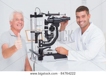 Portrait of happy senior man showing thumbs up while sitting with optician in clinic