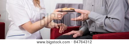 Care Assistant Giving Pensioner Cookies