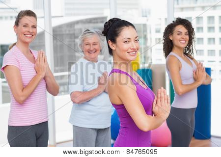 Side view portrait of female friends with hands clasped standing in gym