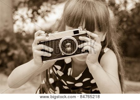 girl taking photographs with vintage camera. Black and white shot.