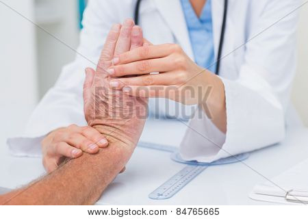 Cropped image of female physiotherapist examining male patients wrist in clinic