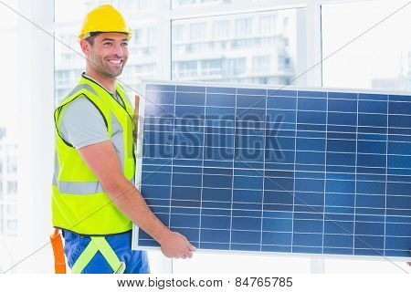 Smiling manual worker in protective clothing carrying solar panel at office