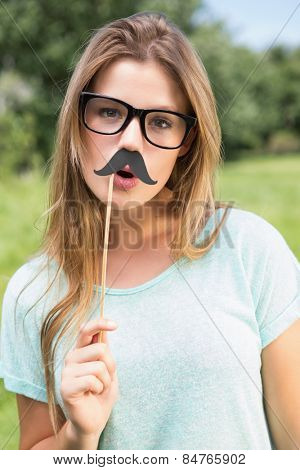 Pretty blonde smiling at camera with fake mustache on a sunny day