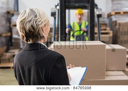 Rear view of warehouse manager in front of her colleague in a large warehouse