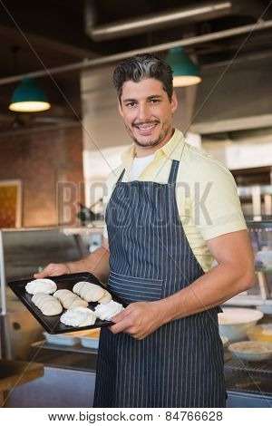 Smiling worker in apron holding tray of meringue at the bakery
