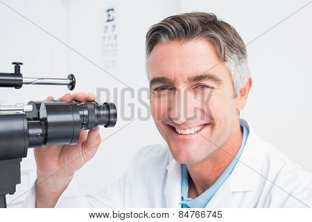 Portrait of happy optician using slit lamp in clinic