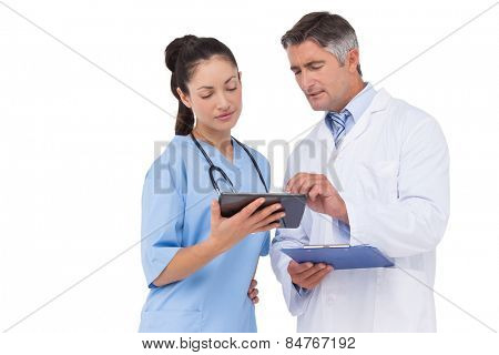 Doctor and nurse looking at clipboard on white background