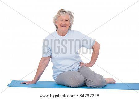 Senior woman smiling on exercise mat on white background