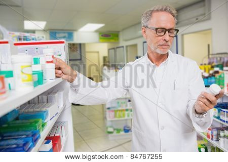 Concentrated pharmacist looking at medicine in the pharmacy