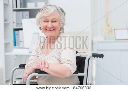 Portrait of happy senior woman sitting on wheelchair in clinic
