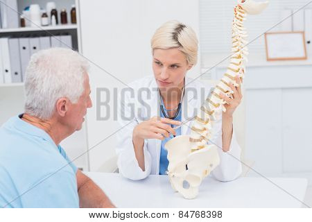 Female doctor explaning spine model to senior male patient in clinic
