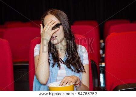 Young woman watching a scary 3d film at the cinema