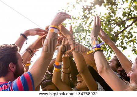 Music fans with their hands up on a sunny day