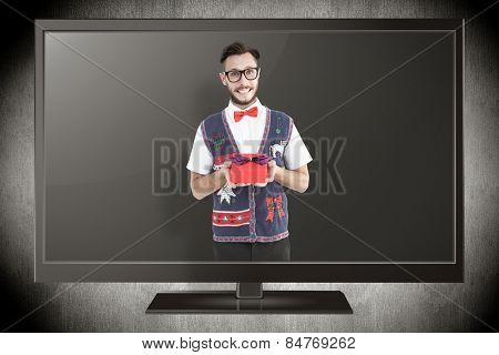 Geeky hipster offering christmas gift against grey vignette