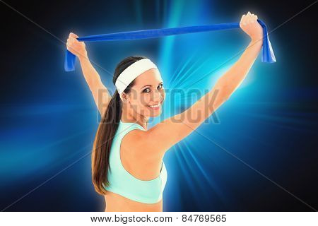 Fit young woman holding up a blue yoga belt against abstract background
