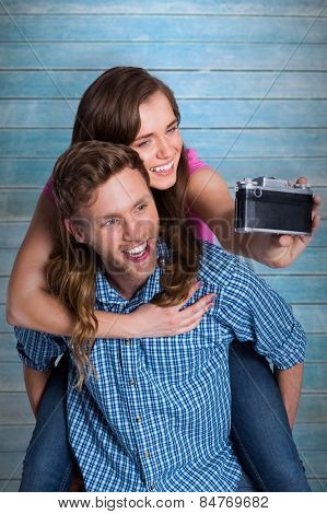 Couple taking selfie with digital camera against wooden planks