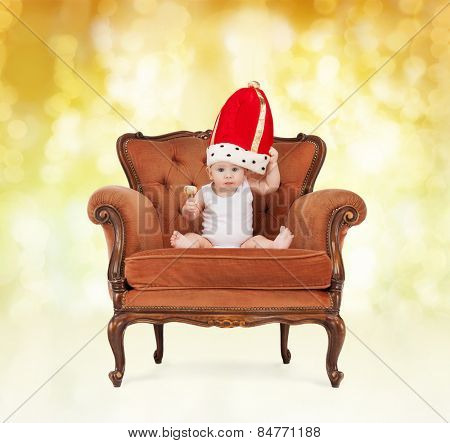 people, childhood, holidays and royalty concept - happy baby boy in royal hat with lollipop sitting on chair over yellow lights background