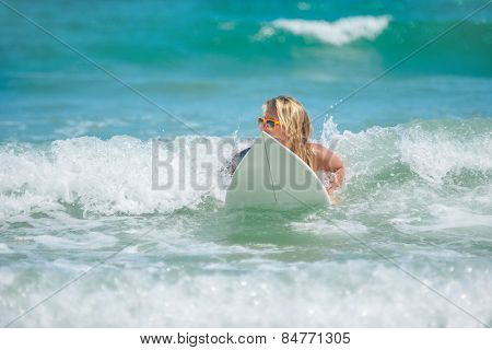 Portrait of a female surfer on her surfboard in the water in action