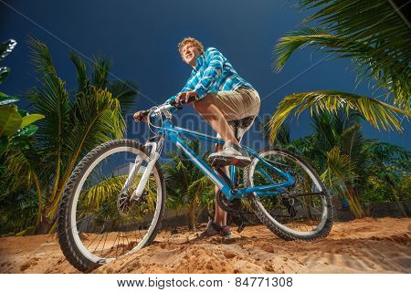 Sport bike cyclist doing extreme biking on the palm trees background