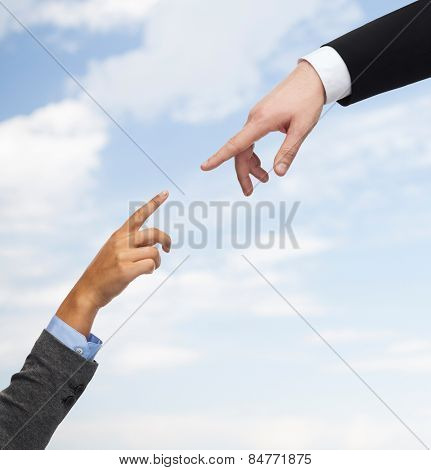 business, people, cooperation and connection concept - close up of woman and man hands trying to connect over blue sky background