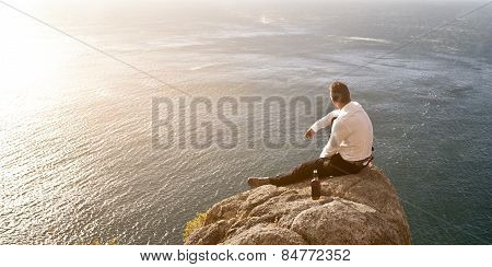 Young handsome man on top of world looking at ocean below