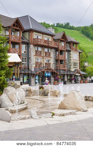 COLLINGWOOD, ON, CANADA - JUNE 18: View of Blue Mountain Village with fountain and shops in summer, 2014.