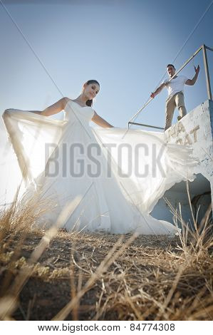 Young happy bridal couple having fun outdoors in long grass