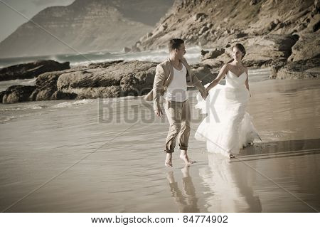 Young happy couple having fun on beach at sunrise