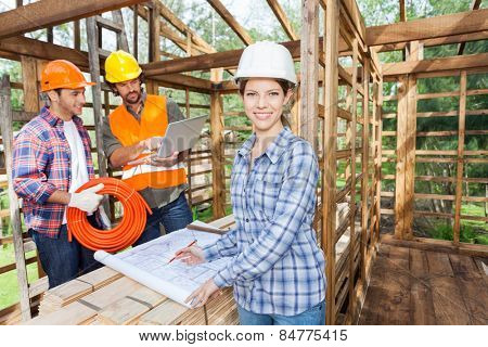 Portrait of confident female architect working on blueprint with male colleagues using laptop in incomplete wooden cabin at site