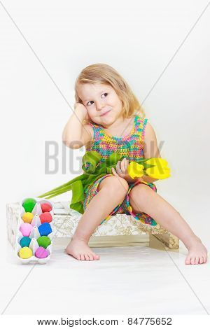 Little girl holding tulips with Easter eggs