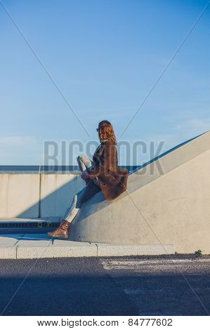 Woman Sitting On Barrier In The Road