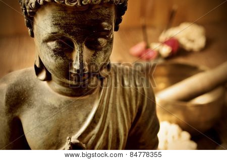 closeup of a buddha with flowers in the background as offerings