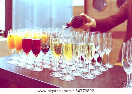 Bartender is pouring sparkling wine in glasses, making cocktails, toned image