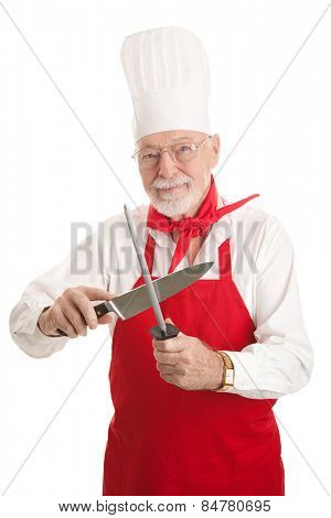 Handsome experienced chef sharpening his knife.  Isolated on white.