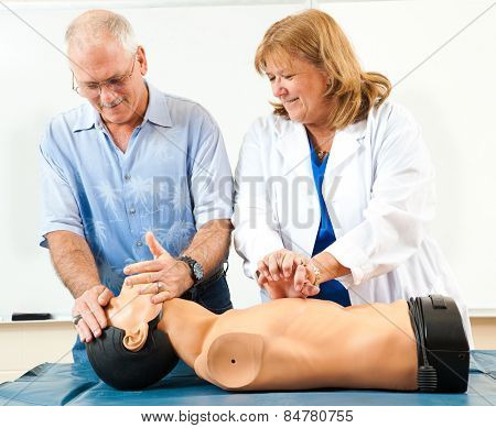 Doctor teaching CPR to a mature student.