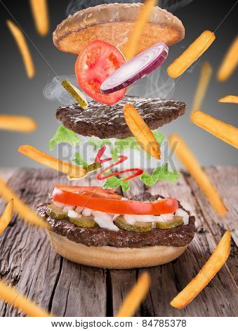 French fries with burger in freeze motion isolated on white