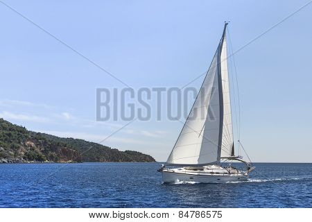 Sailing in the wind through the waves. Yachting in the Mediterranean Sea.