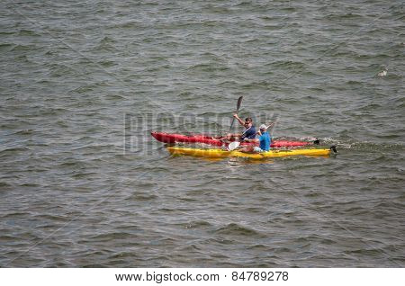 Canoes With Unidentified People Rowing In The Sea